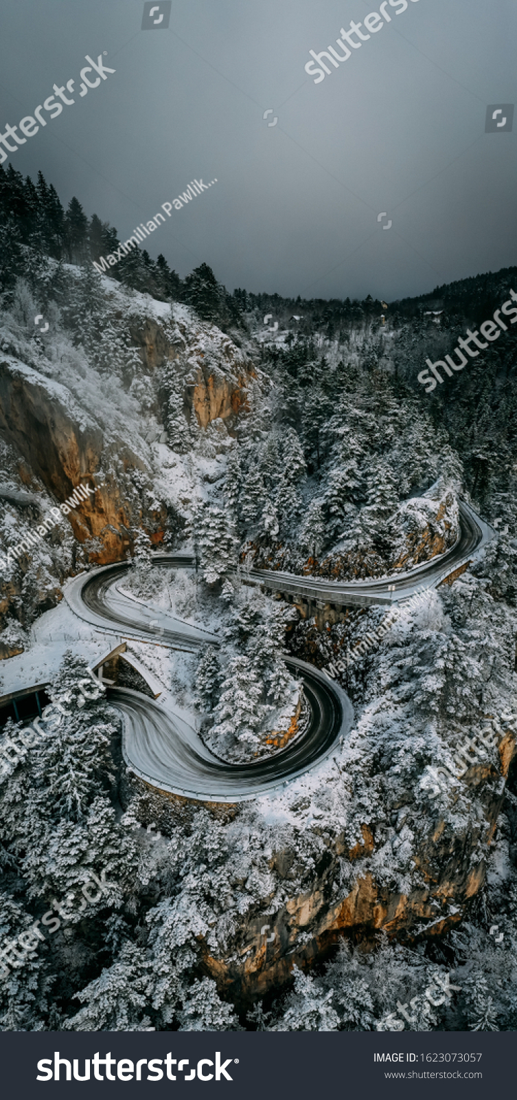 Curvy windy mountain road in snow covered forest, top down aerial view. Winter landscape. #1623073057