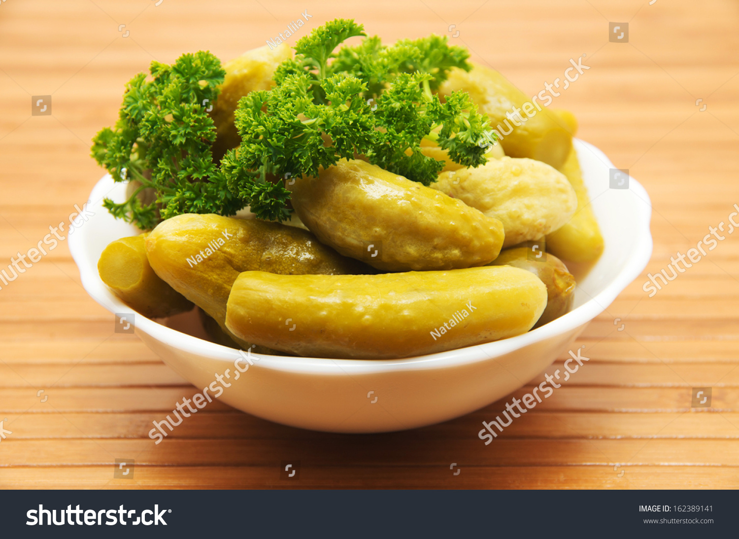 Plate with small canned gherkins on wooden background. #162389141