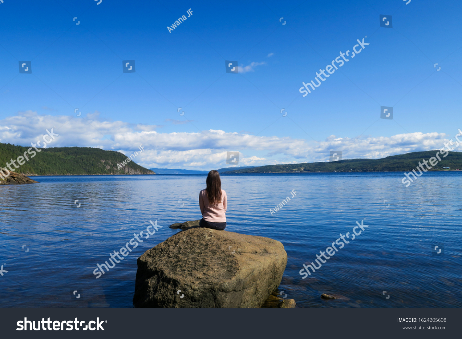 Beautiful young woman sitting in peace on a rock contemplating the Saguenay fjord
