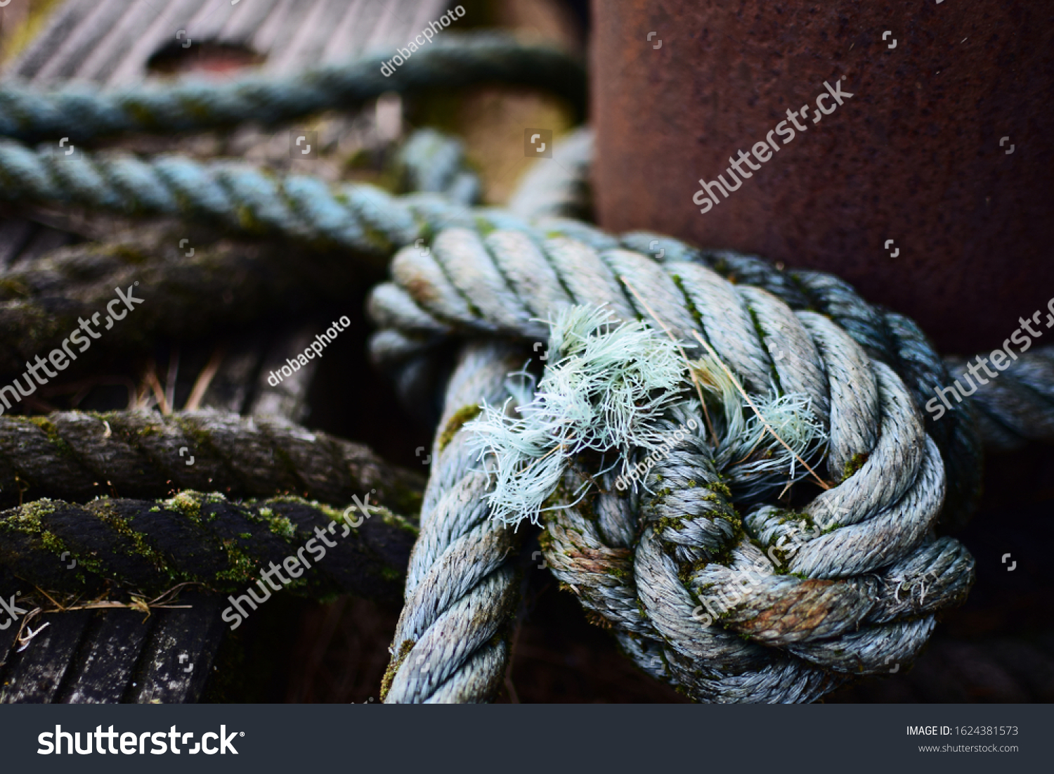 Rough rope knotted around rusty bollard. Old moored ropes