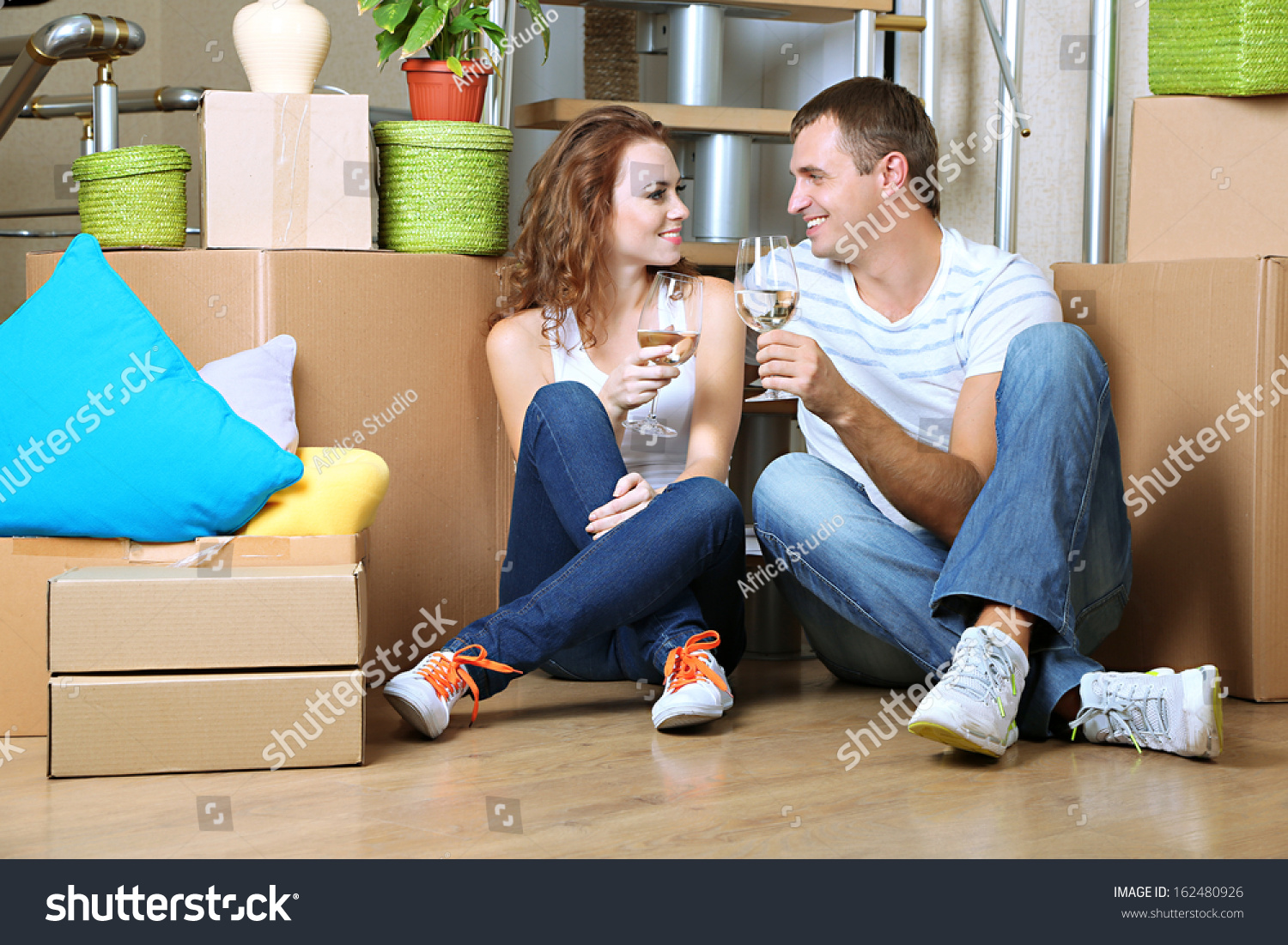 Young couple celebrating moving to new home sitting among boxes stock photo 162480926 shutterstock - Young couple modern homes ...