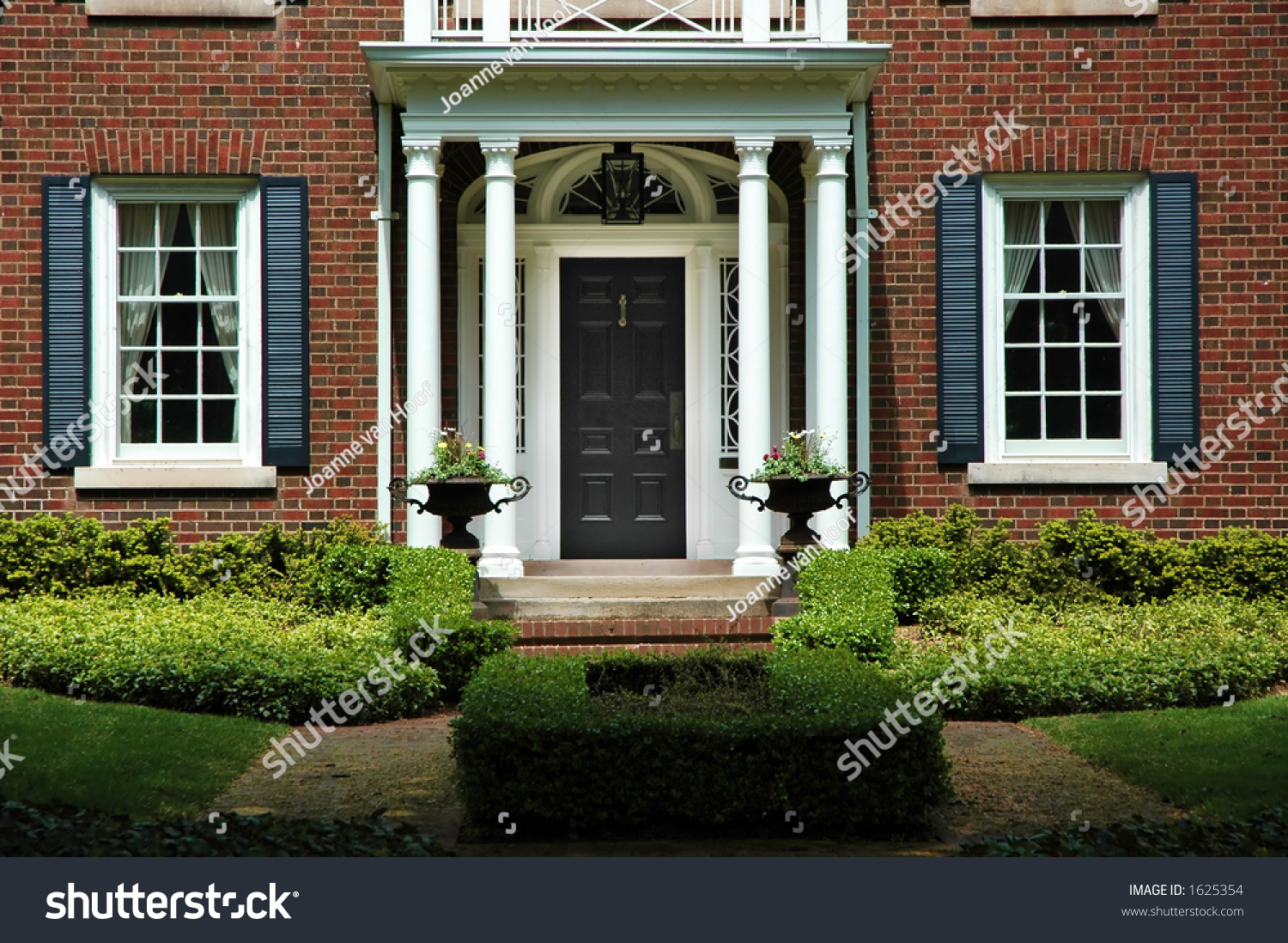 Red front door on brick house - Red Brick House With Black Shutters And Green Shrubs With Front Door Flanked By Pillars And