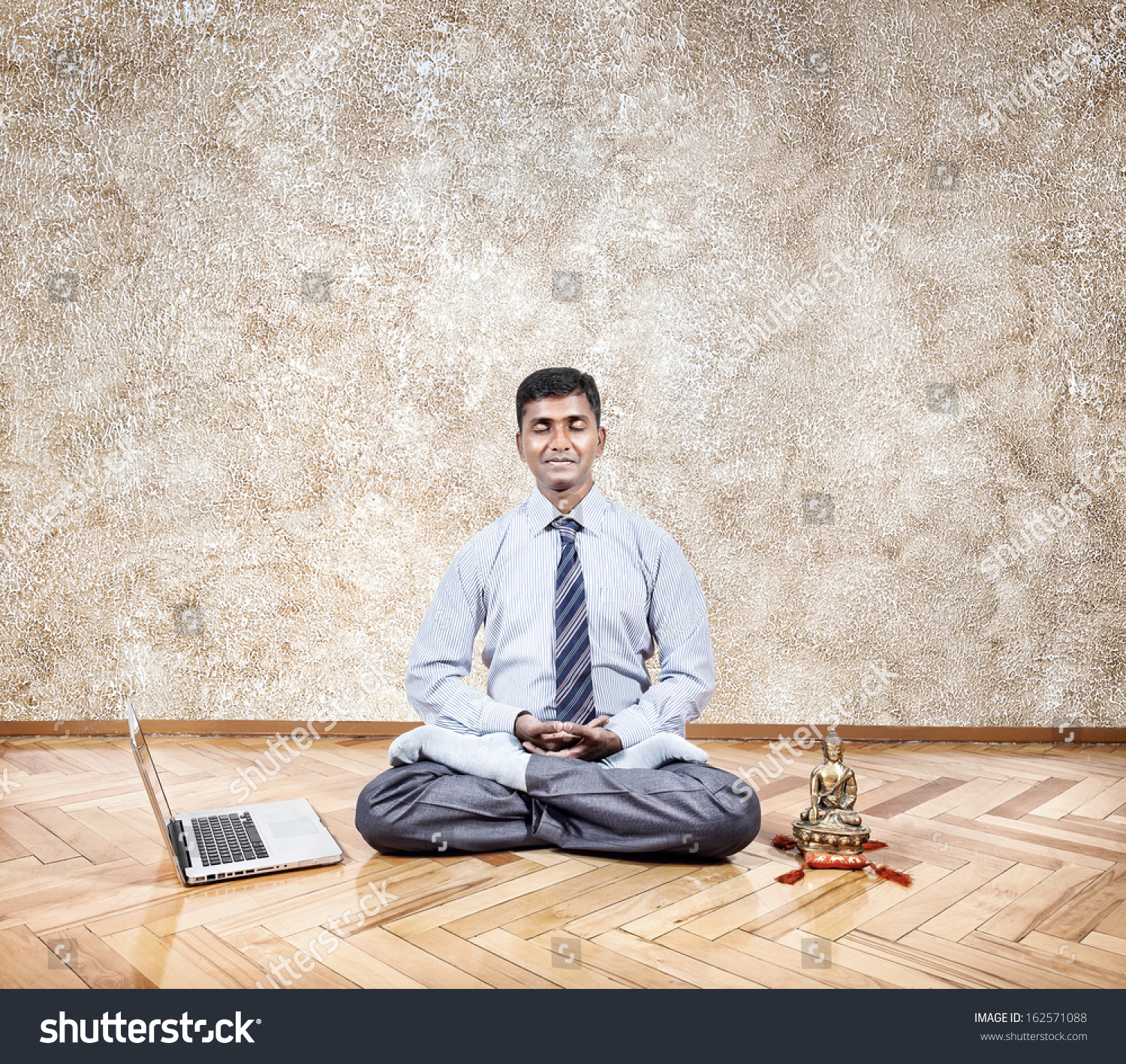 office meditation. office meditation businessman doing nearby laptop and buddha statue in the flmb inside