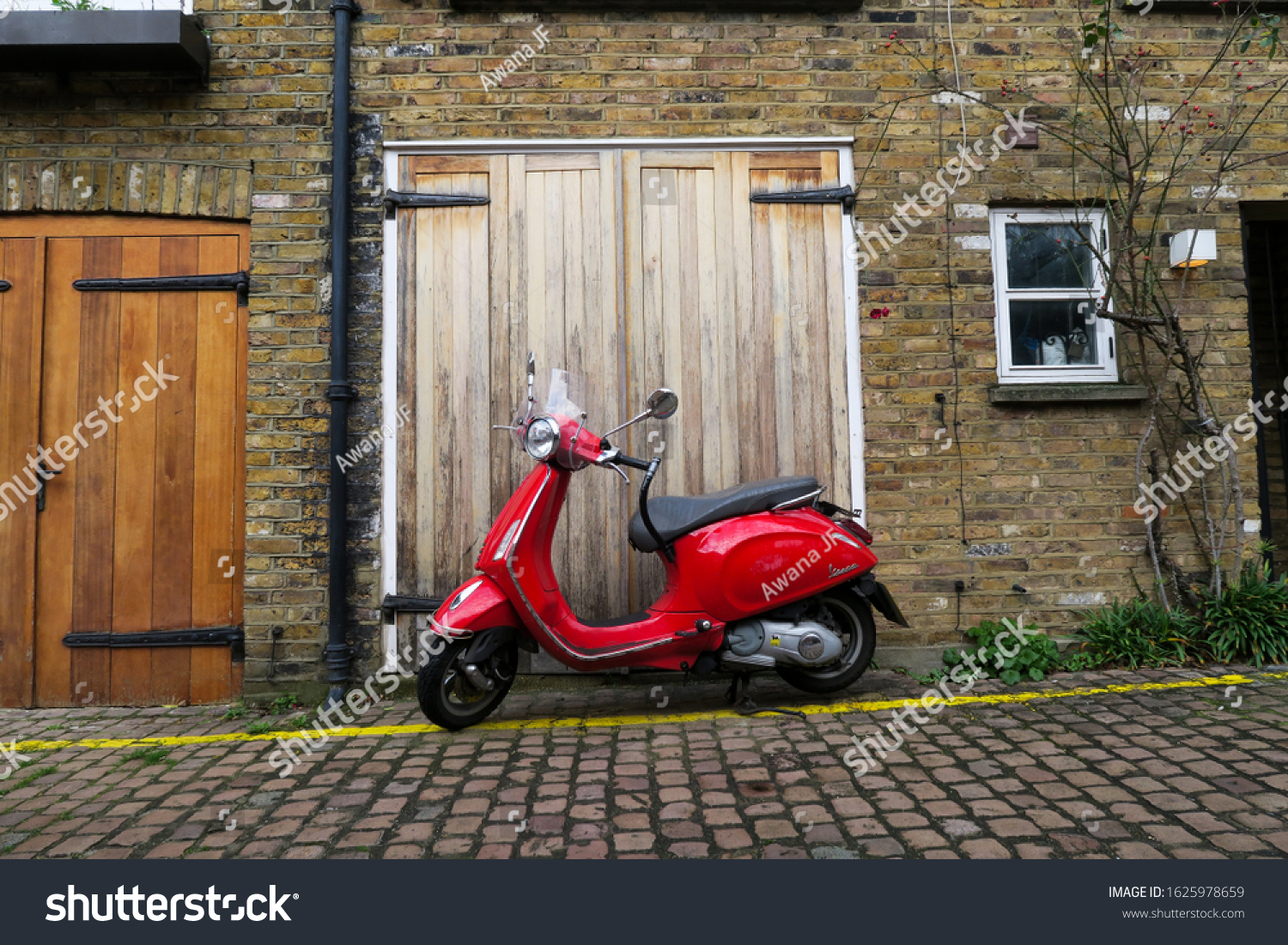 London, UK - january 2020: red vintage scooter parked in front of a wooden garage door