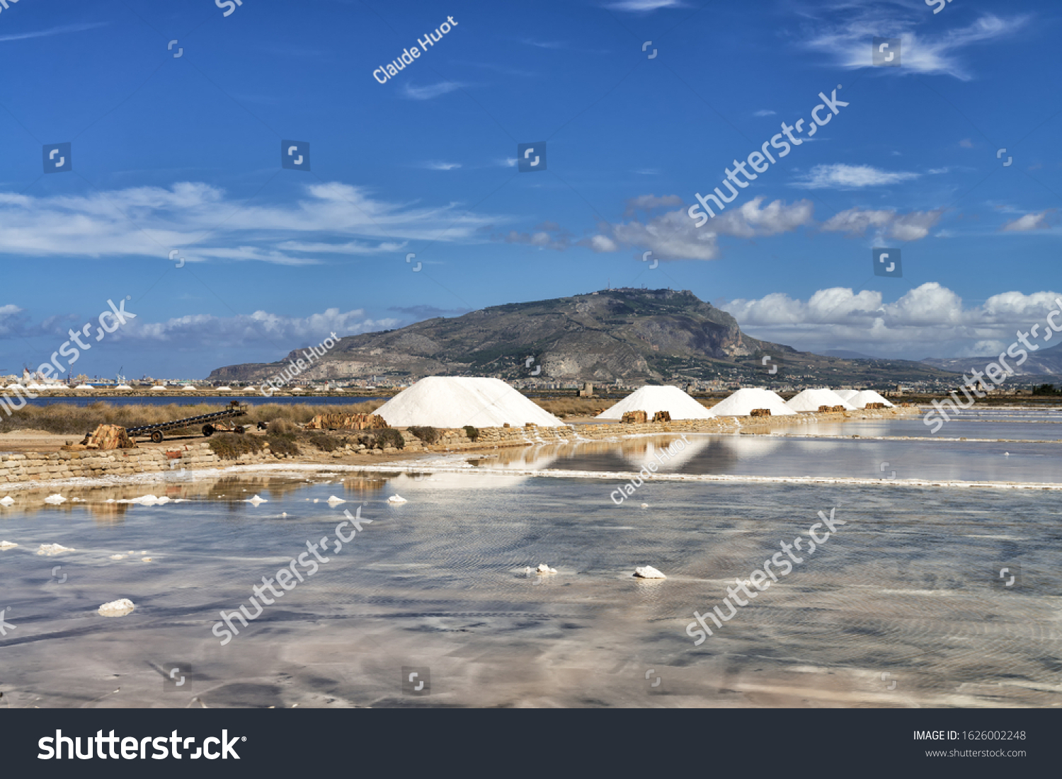 Salt monds and pans in the region of Trapani and Paceco in Sicily, Italy. The salt production from seawater is a big industry here. The city of Erice is on top of the mountain in the background.