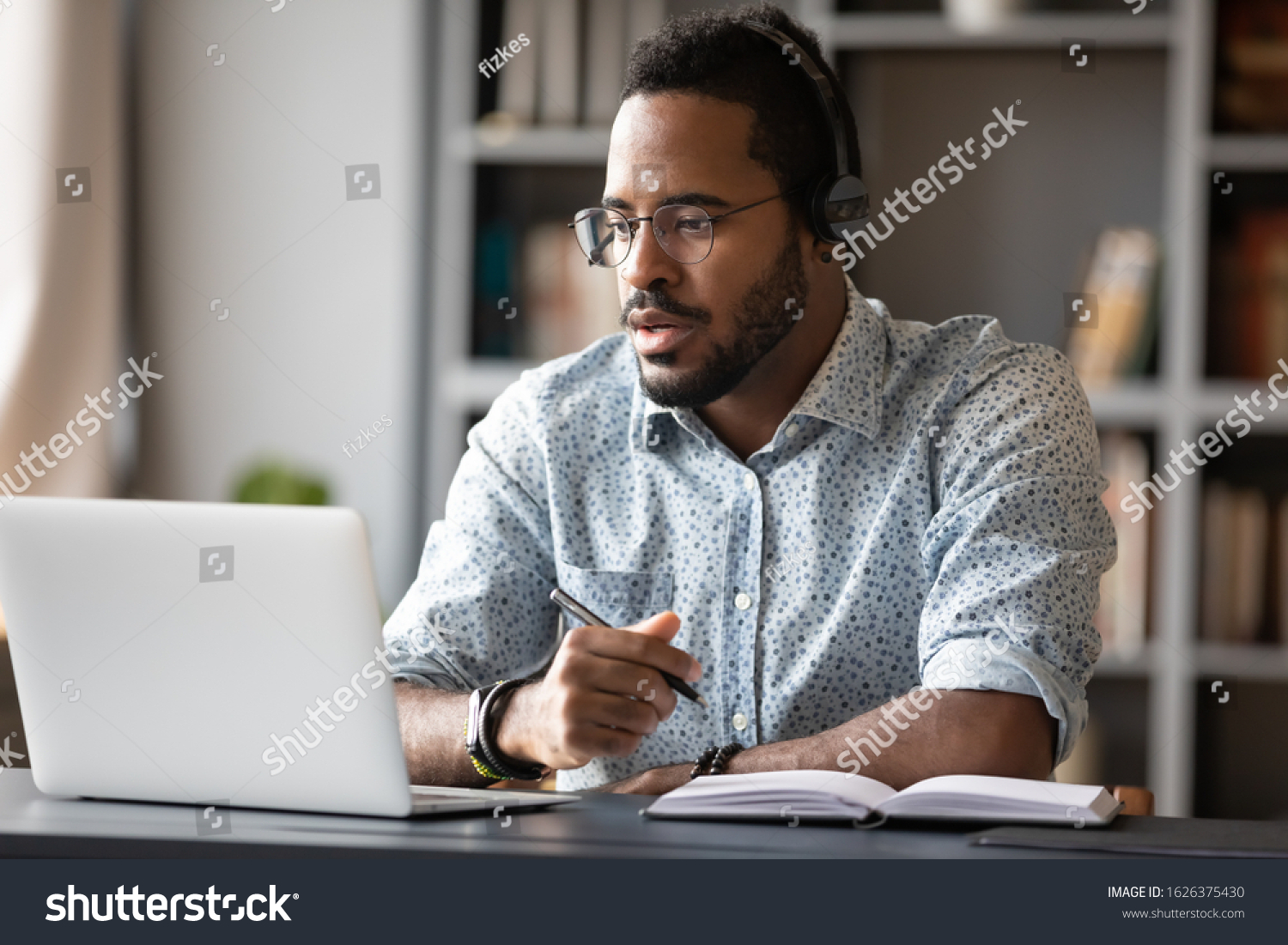Focused young african businessman wear headphones study online watching webinar podcast on laptop listening learning education course conference calling make notes sit at work desk, elearning concept #1626375430