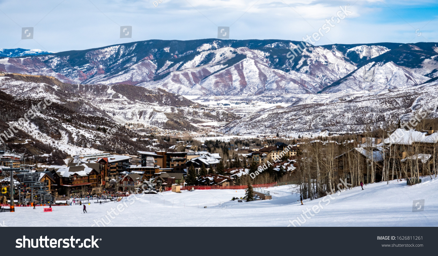 Panoramic view of Snowmass Village, with skiers skiing at the Aspen Snowmass ski resort in the foreground and the Rocky Mountains of Colorado in the background, on a partly cloudy winter day.
