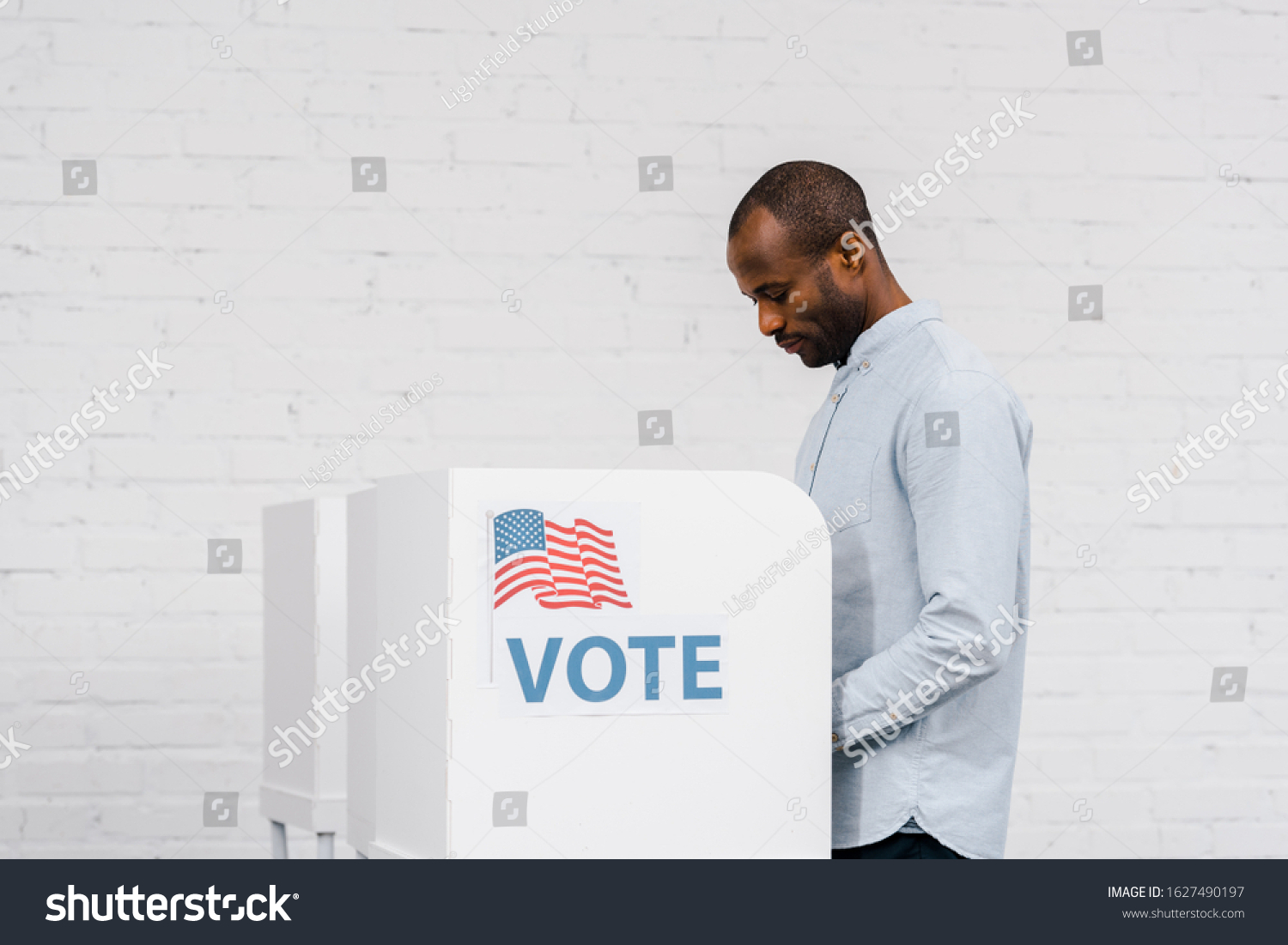 african american citizen voting near stand with vote lettering #1627490197