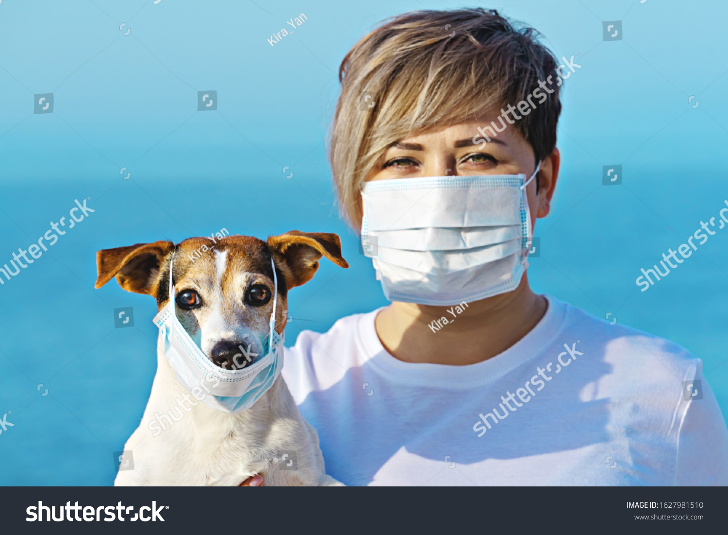 Woman in protective surgical mask holds dog pet in face mask. Chinese Coronavirus disease COVID-19 is dangerous for pets #1627981510