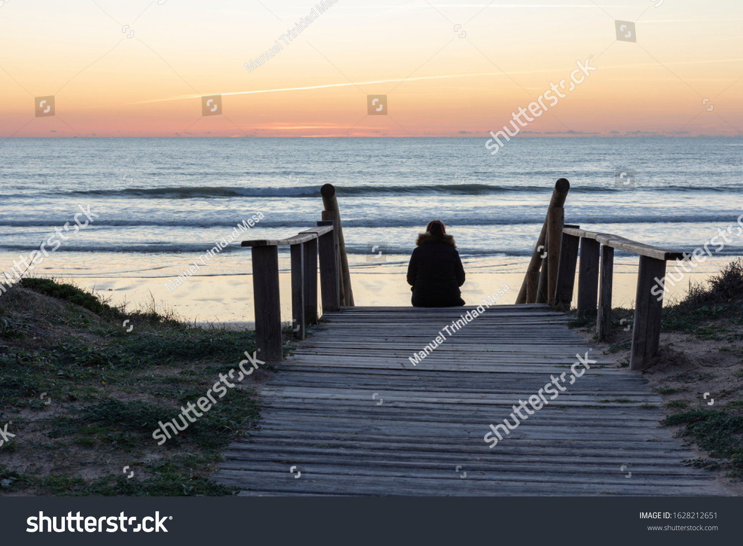 Woman watching the sunset on the beach