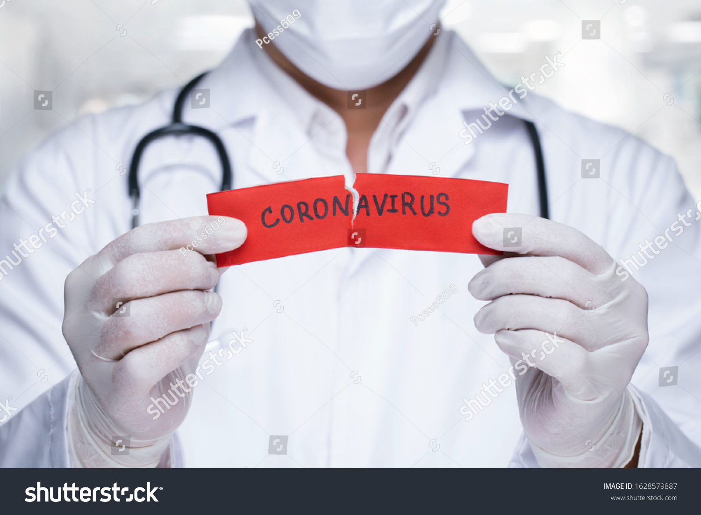 Concept of coronavirus quarantine. MERS-Cov.Novel coronavirus (2019-nCoV).Doctor with a stethoscope Tear the red paper with the word coronavirus.       #1628579887