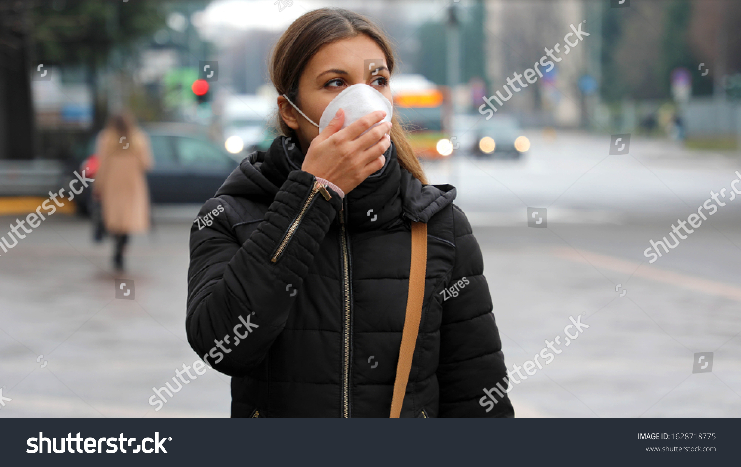 COVID-19 Pandemic Coronavirus Woman in city street wearing face mask protective for spreading of disease virus SARS-CoV-2. Girl with protective mask on face against Coronavirus Disease 2019. #1628718775