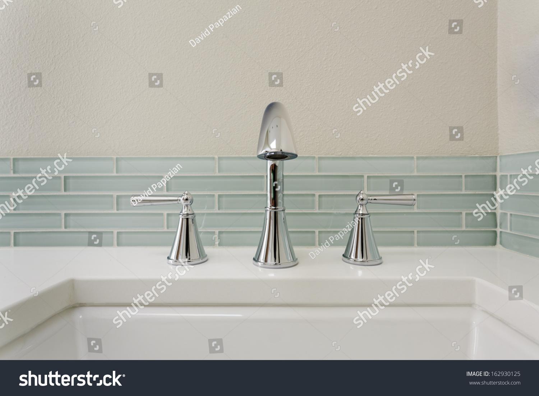 Pale blue bathroom - A Bathroom Sink With Chrome Fixture Shown Against Pale Blue Subway Tile