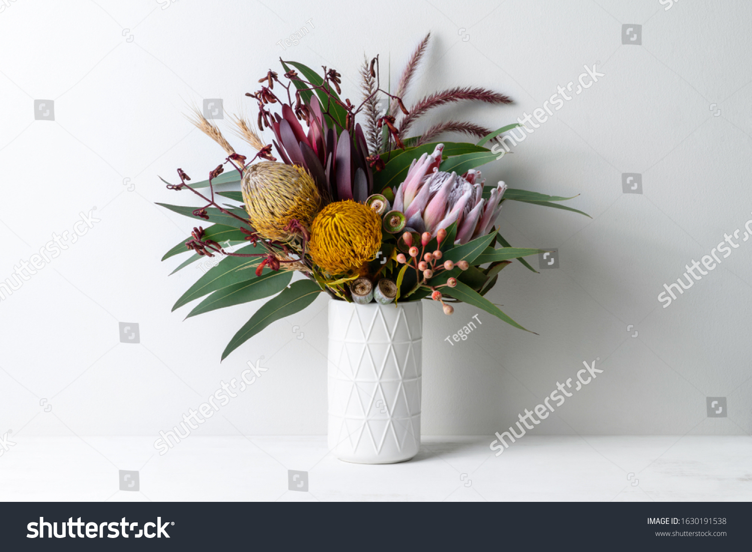 Beautiful floral arrangement of mostly Australian native flowers, including protea, banksia, kangaroo paw, eucalyptus leaves and gum nuts, in a white vase on a white table with a white background. #1630191538