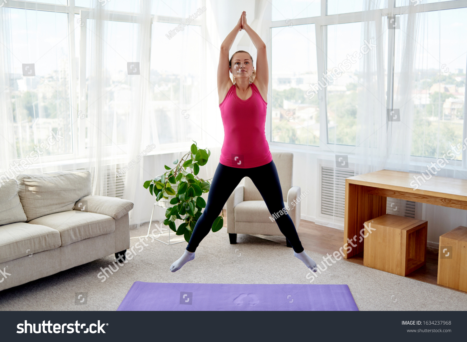 Young fitness woman doing jumping jacks or star jump exercise at home, copy space. Girl working out, full length portrait. Healthy lifestyle concept #1634237968