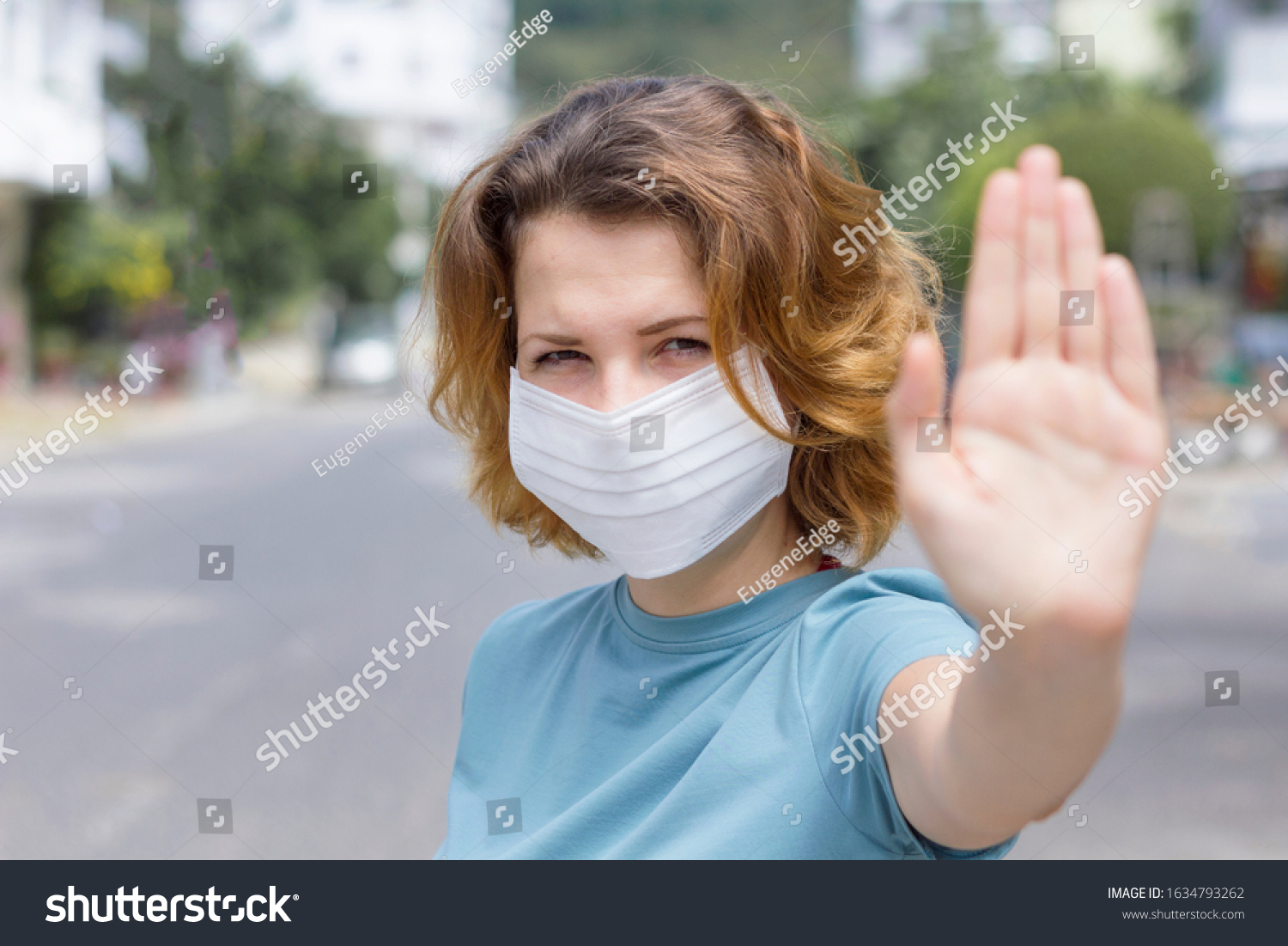 Girl, young woman in protective sterile medical mask on her face looking at camera outdoors, on asian street show palm, hand, stop no sign. Air pollution, virus, Chinese pandemic coronavirus concept. #1634793262