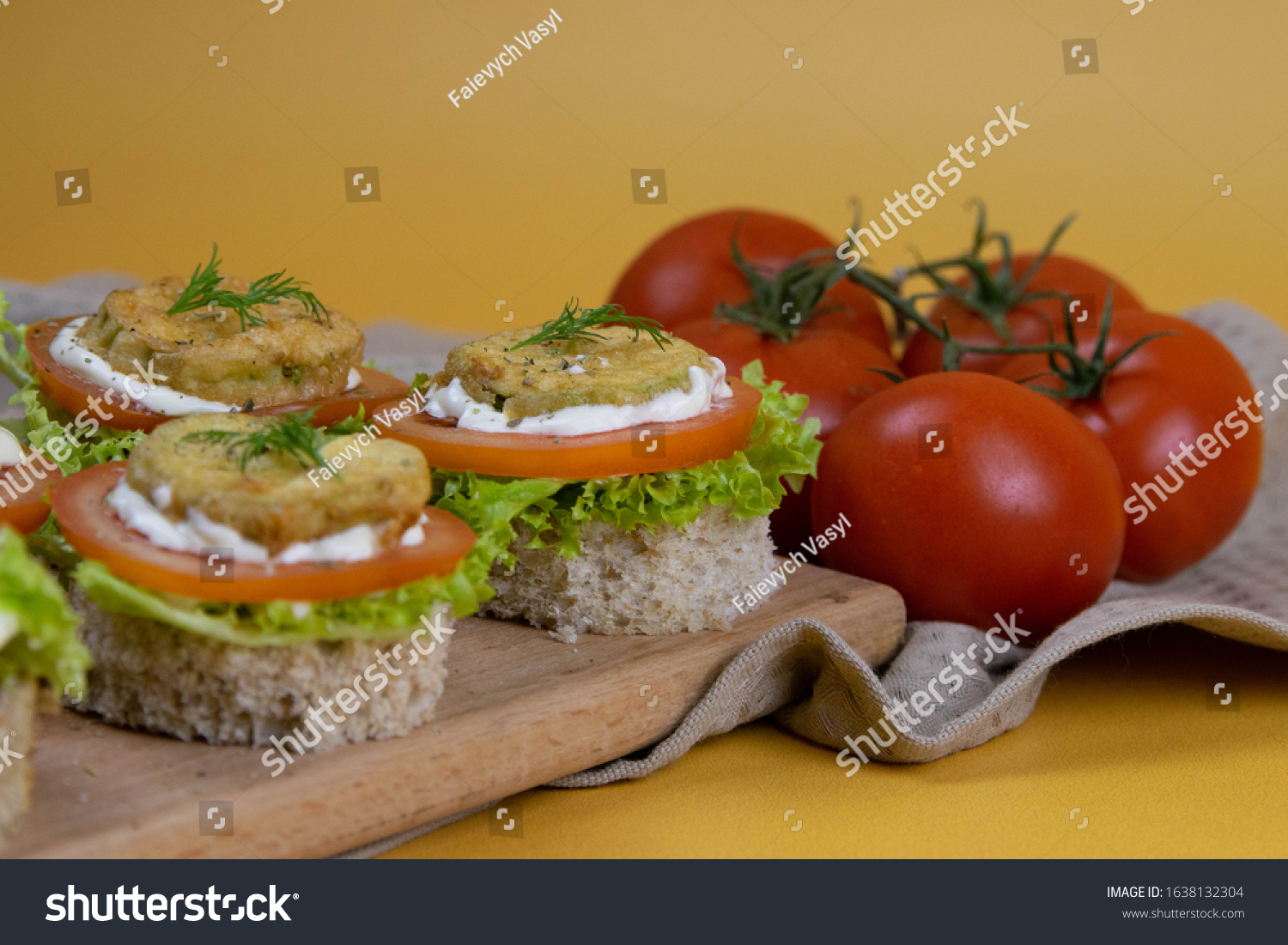 Sandwich with lettuce, cheese, tomatoes and roasted courgettes, on top is a piece of dill, all standing on a wooden board on an orange background. Front views #1638132304