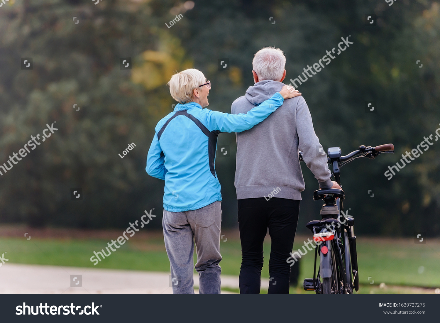 Cheerful active senior couple with bicycle walking through park together. Perfect activities for elderly people. #1639727275