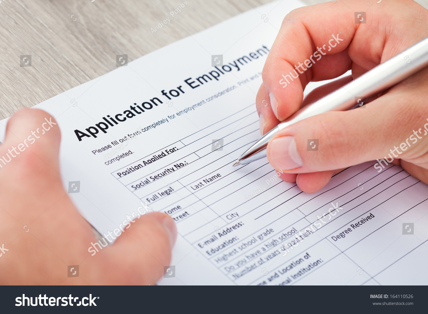 close up of hand filling application for employment stock photo close up of hand filling application for employment