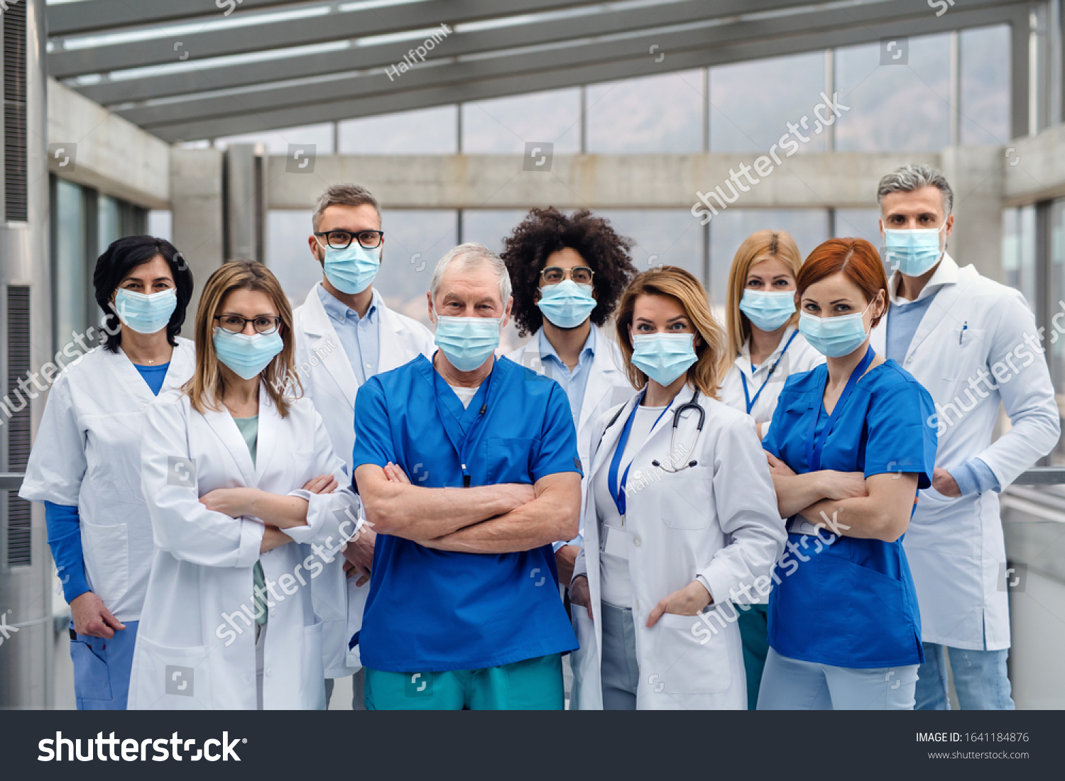 Group of doctors with face masks looking at camera, corona virus concept. #1641184876