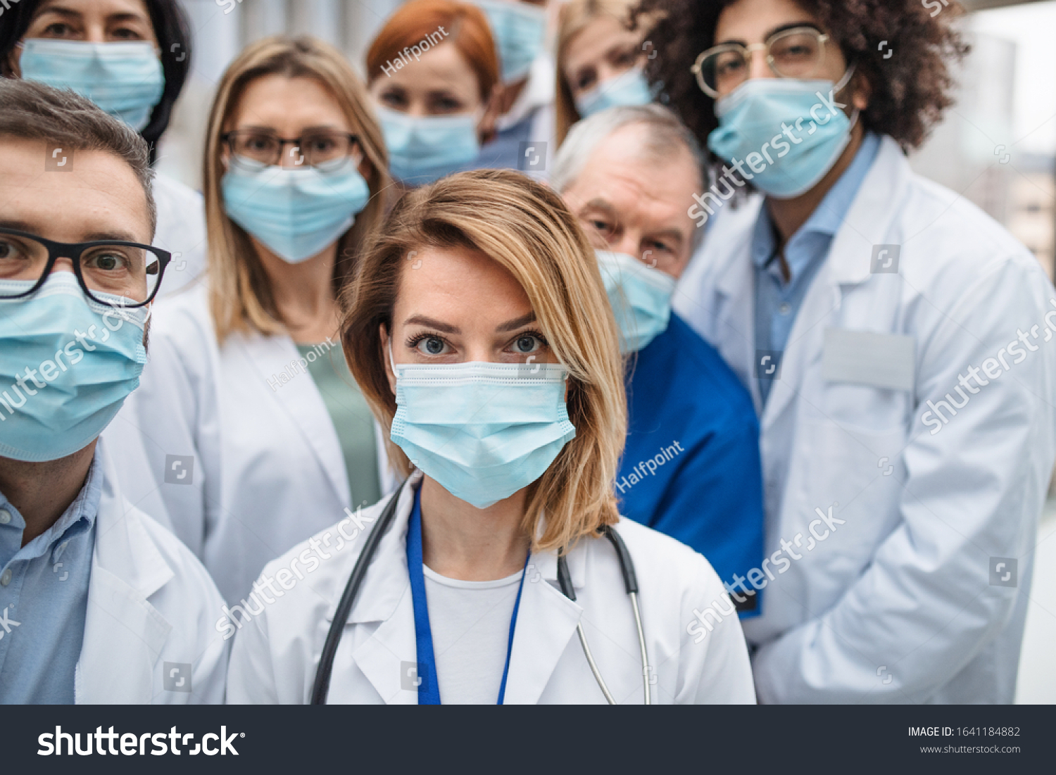 Group of doctors with face masks looking at camera, corona virus concept. #1641184882