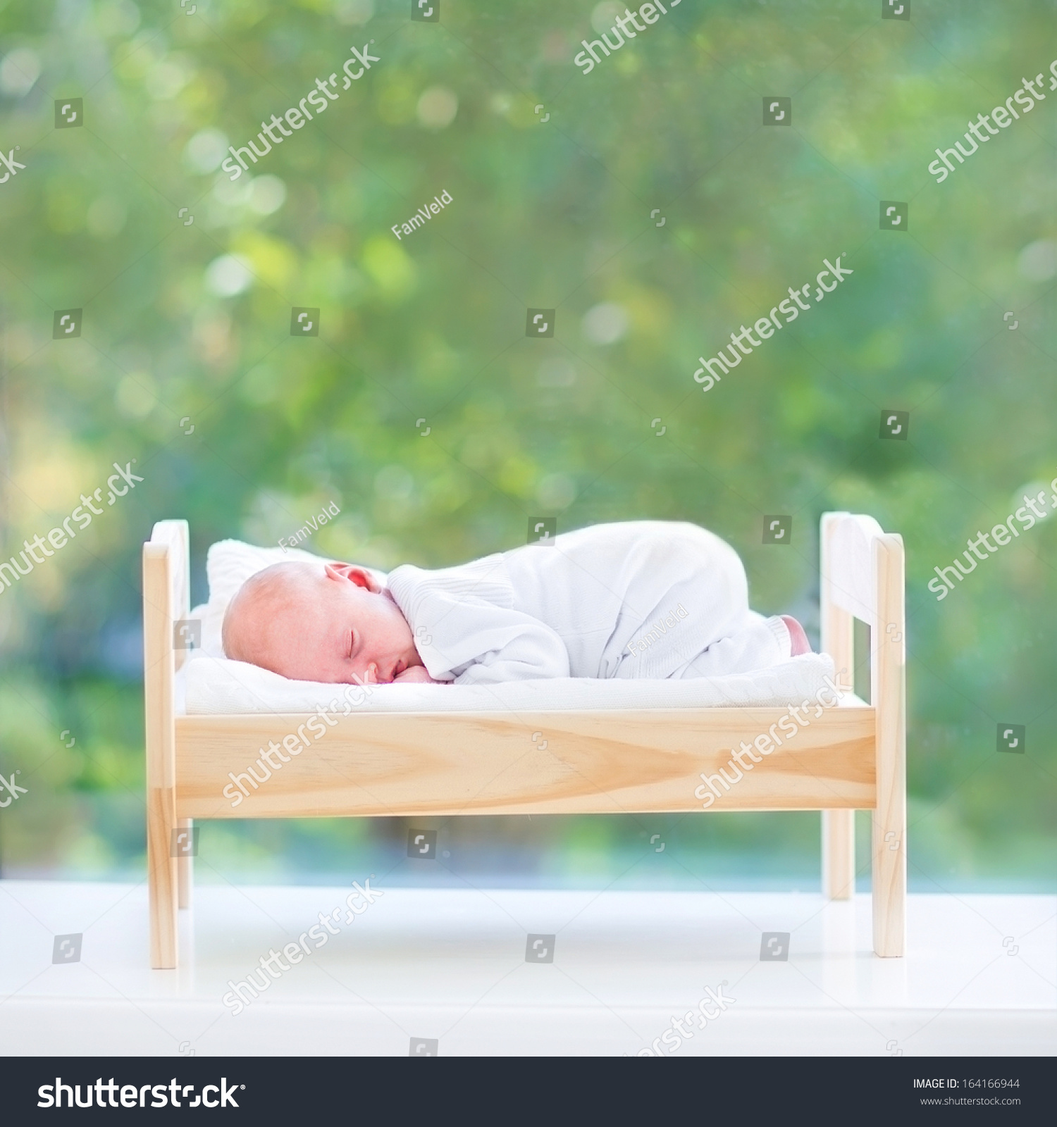 Baby Bed Next To Bed - Tiny newborn baby sleeping in a toy bed next to a big window into the garden