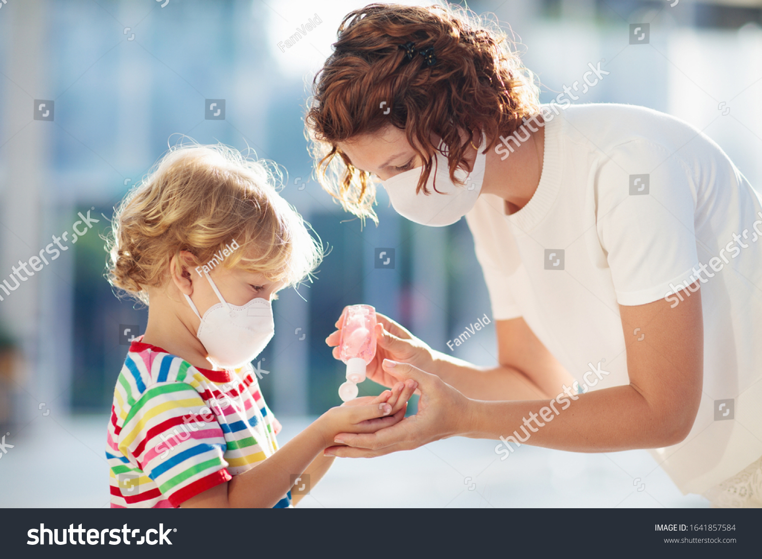 Family with kids in face mask in shopping mall or airport. Mother and child wear facemask during coronavirus and flu outbreak. Virus and illness protection, hand sanitizer in public crowded place. #1641857584