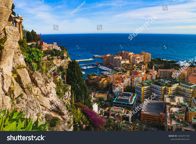 Monaco-Ville, Monaco - January 28, 2020: Monaco cityscape, Fontvielle harbor and the Mediterranean coast framed by lush exotic plants.