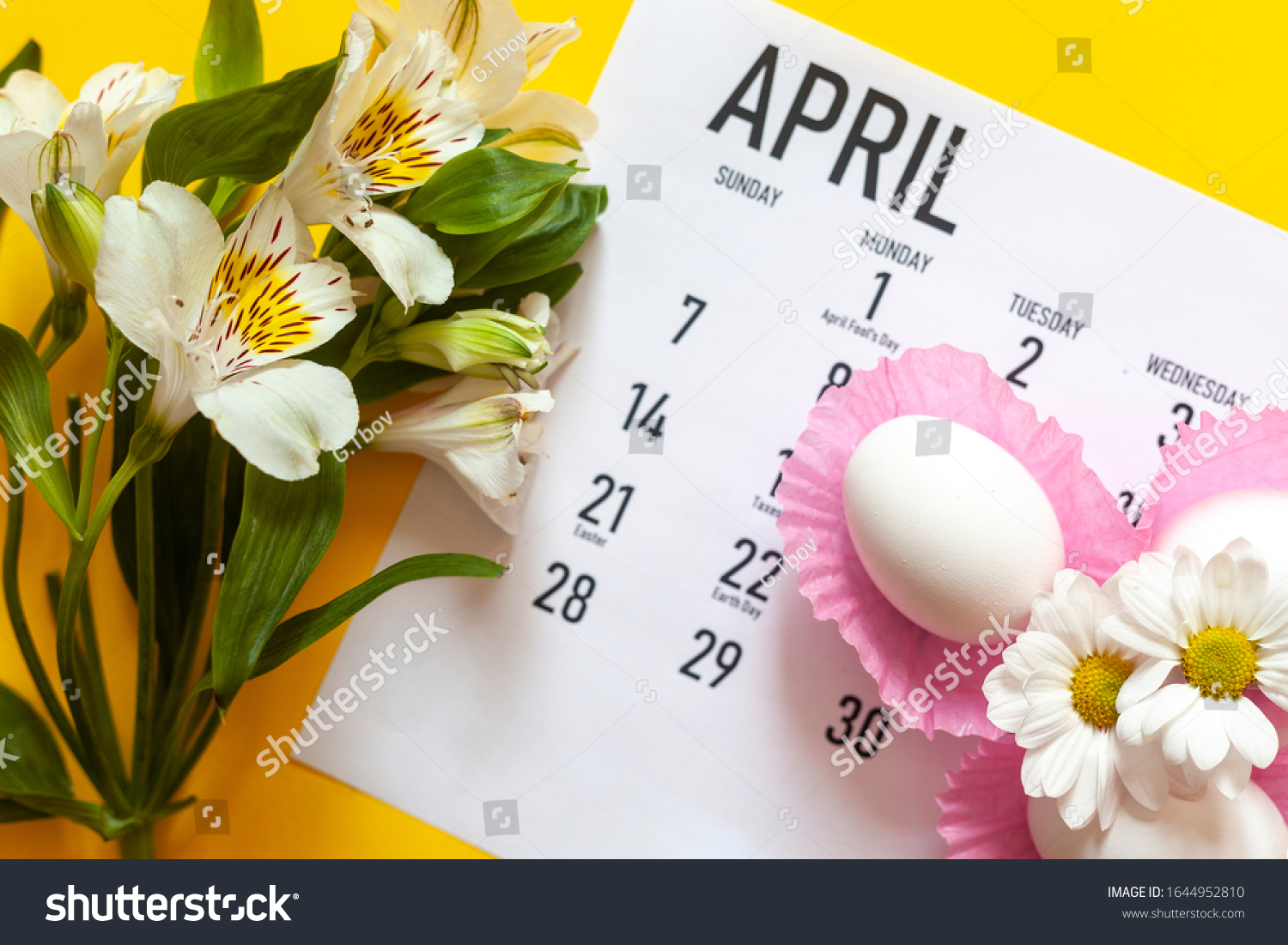 April 2020 calendar, cute pure white easter eggs and white flowers on yellow background. April 2020 monthly calendar. Top view. View from above. Monthly April calendar #1644952810