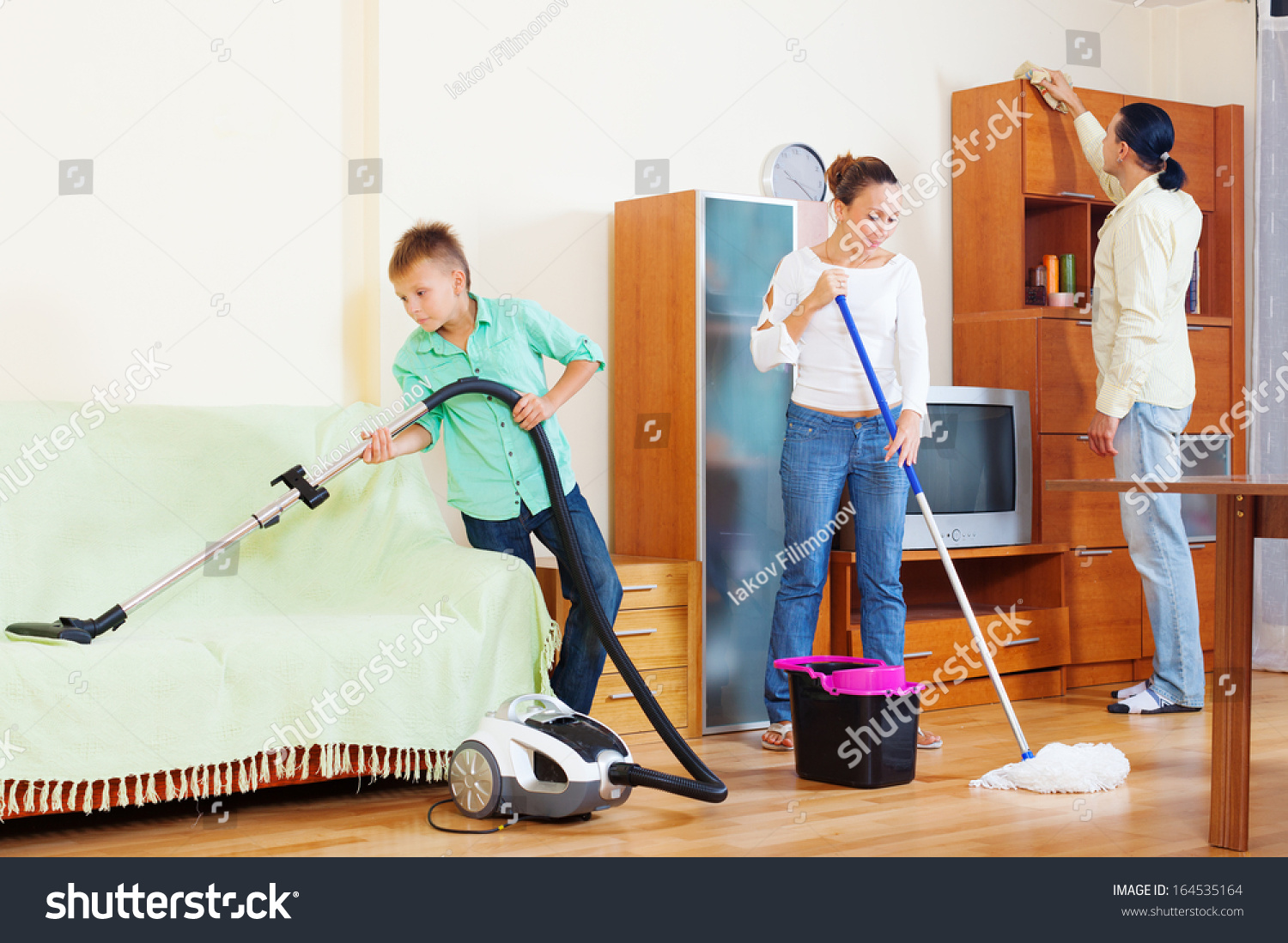 Happy Family Of Three Cleaning With Vacuum Cleaner In Living Room Stock Photo 164535164