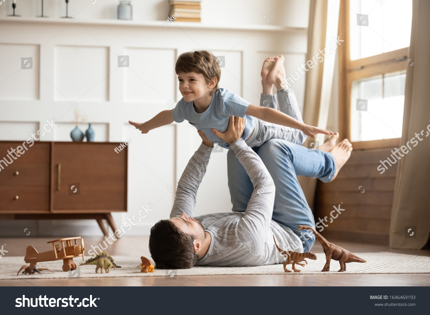 Joyful young man father lying on carpet floor, lifting excited happy little child son at home. Full length carefree two generations family having fun, practicing acroyoga in pair in living room. #1646469193