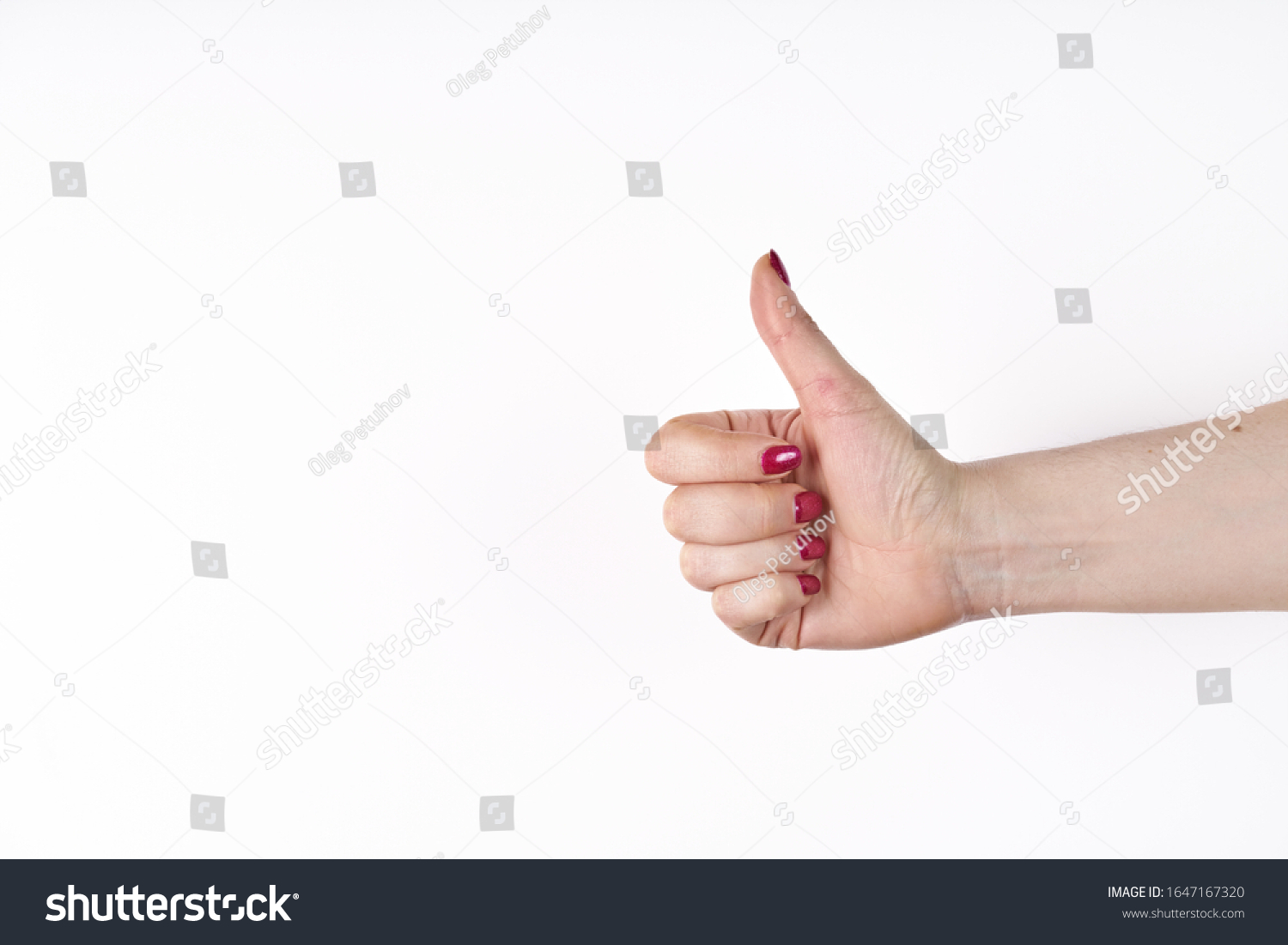 Closeup of female hand showing thumbs up sign against white background. #1647167320