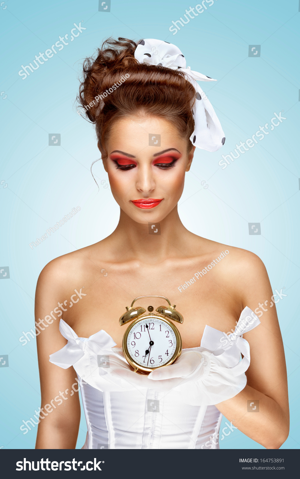 2fa5cf007 A beautiful vintage pin-up girl in a white wedding dress being late in the  morning and holding a retro alarm clock in her hand.