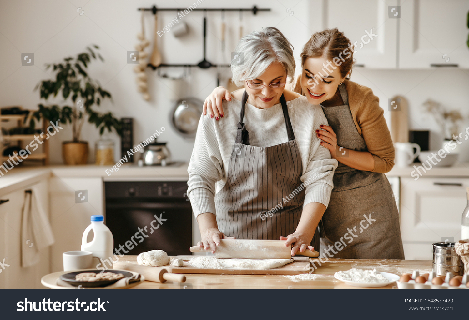 happy family grandmother  old mother mother-in-law and daughter-in-law daughter cook in kitchen, knead dough and bake cookies