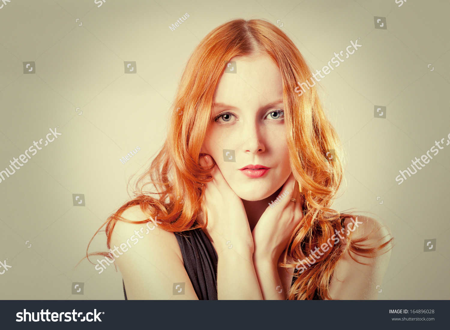 Horizontal beauty shot of a young blue eyed woman with her red hair, touching face by her hands, looks very shy