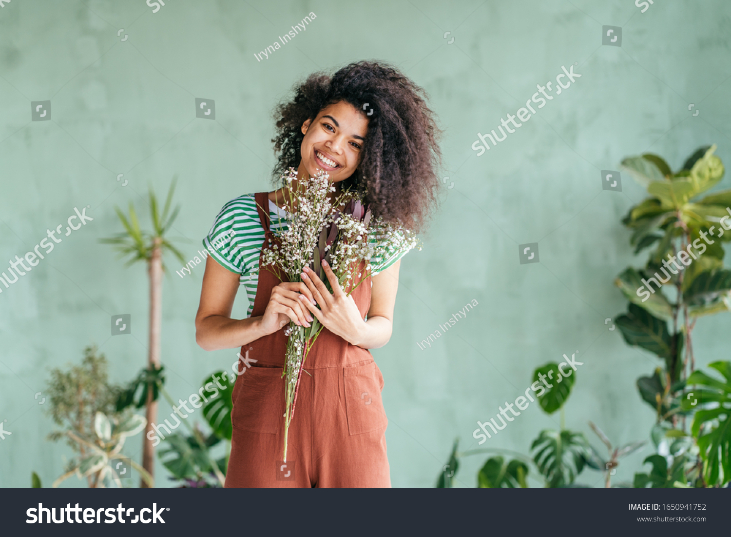 Young woman cultivating home plants.Small business.Sensual mixed race female florist with flowers in hands against background of indoor plants. Life lover, zero waste, inspiration, summer mood concept #1650941752