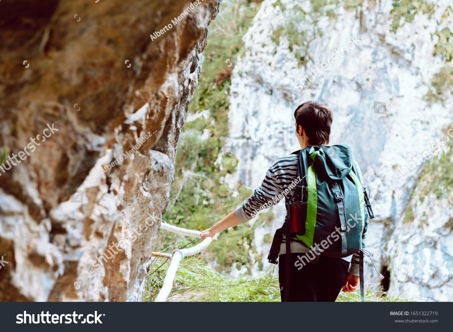 Hiker clutching a safety rope during his ascent to the mountain. Lifestyle concept. #1651322719