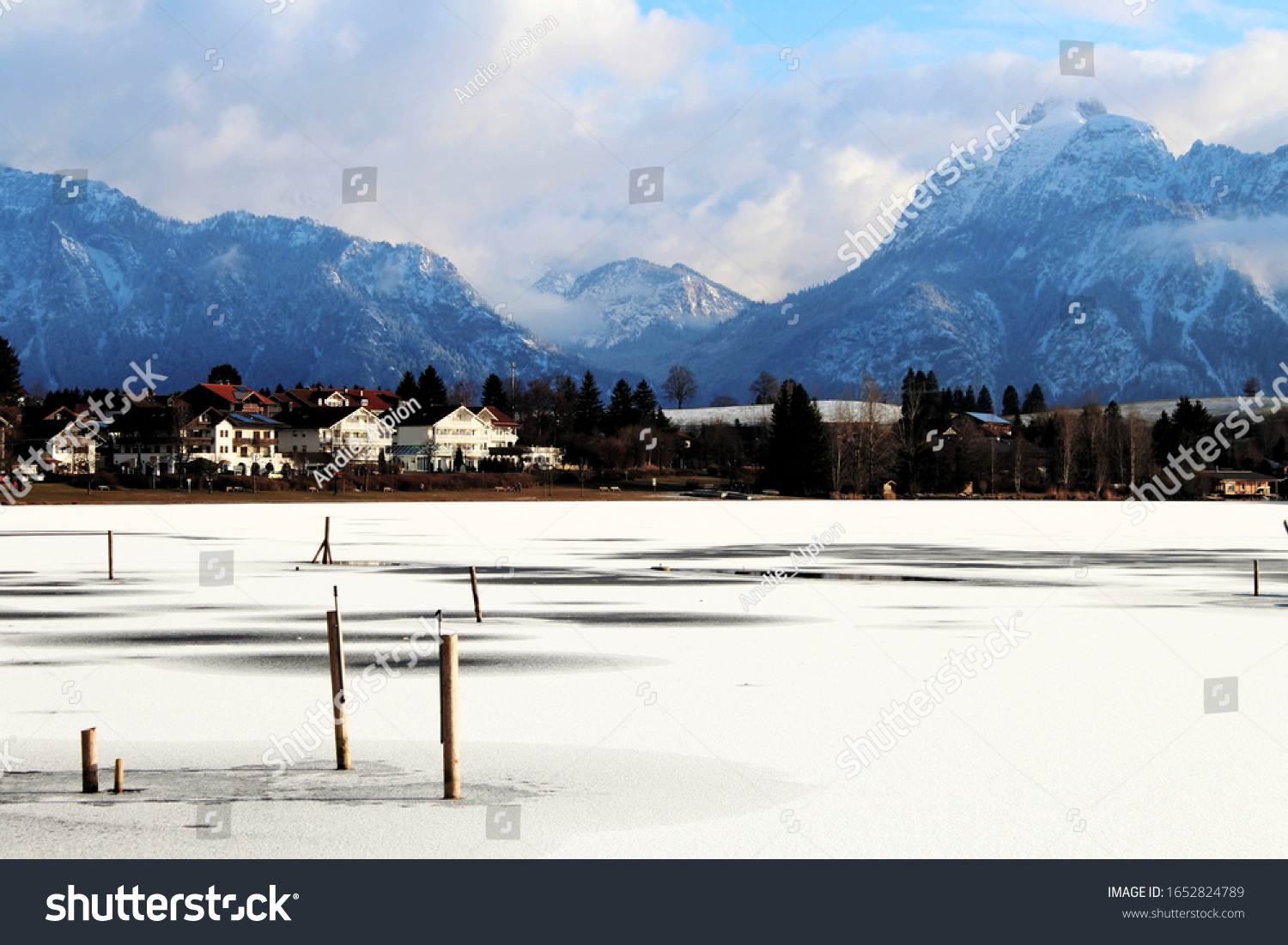 View over a frozen lake in Winter, buildings on the left side, impressive sky, blue mountains in the background, Allgäu, Bavaria