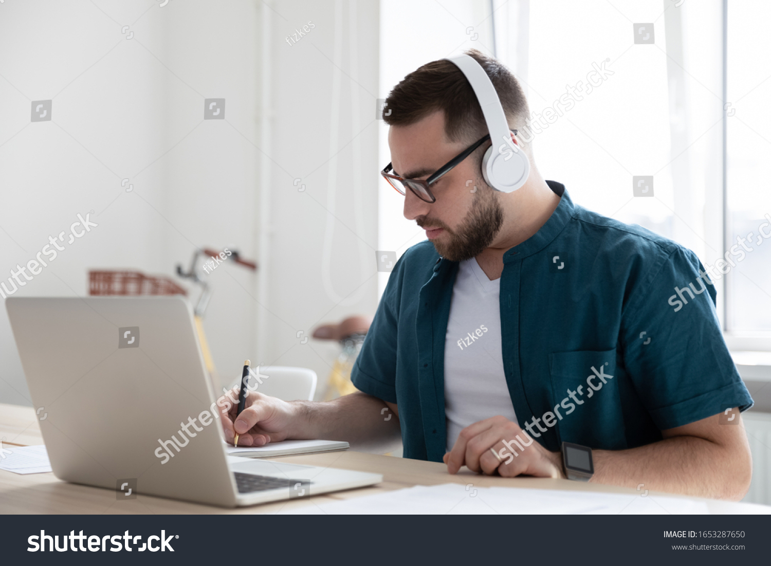 Focused young man businessman company worker employee in glasses wearing wireless headphones, watching educational webinar lecture seminar on laptop online, writing down notes in modern office. #1653287650