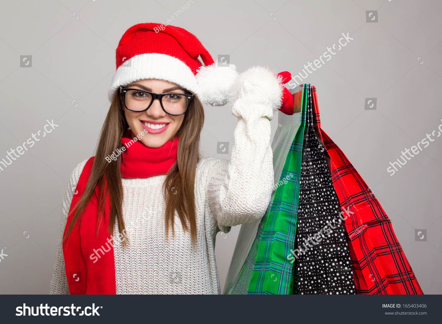 79db83d2efd1b Excited beautiful young Caucasian brunette woman shopping for Christmas  wearing Santa hat and eye glasses holding