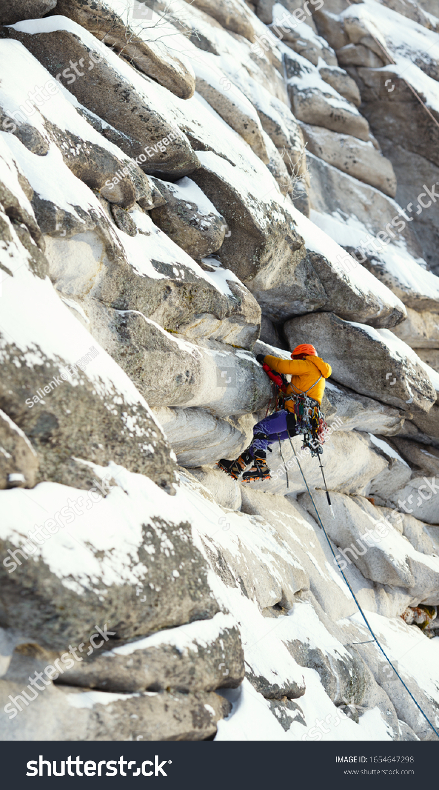 Mountaineer figure in bright outfit climbing up during the winter ascent in the mountains, against the background of overhanging rocks in the foreground and background are out of focus, panorama. #1654647298