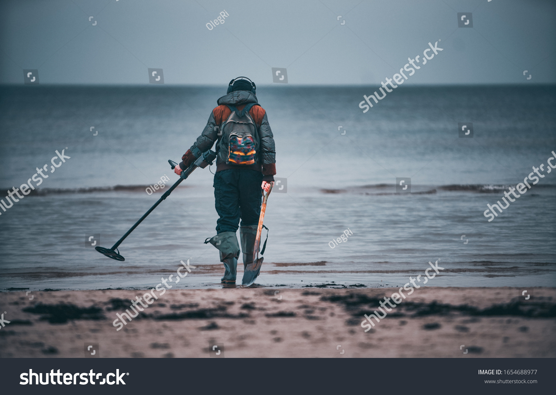 Man with a metal detector on a sea sandy beach. #1654688977