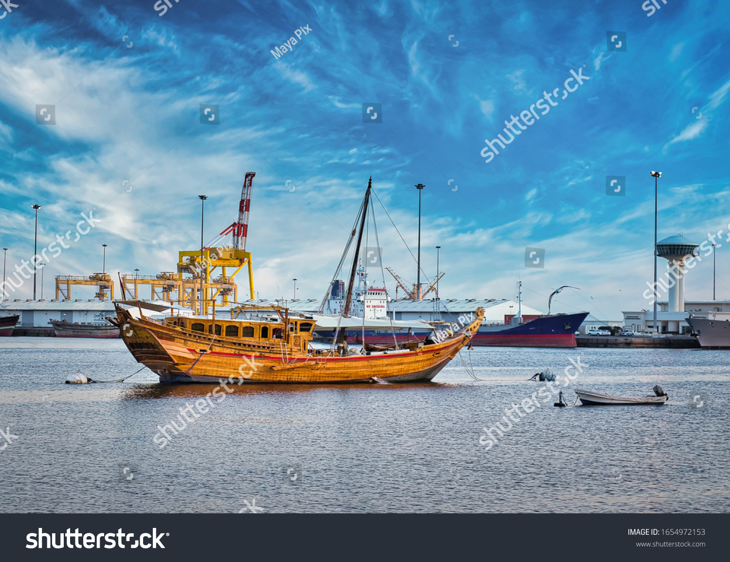 Traditional Omani Dhow anchored at the port along with the modern ships. From Muscat, Oman.