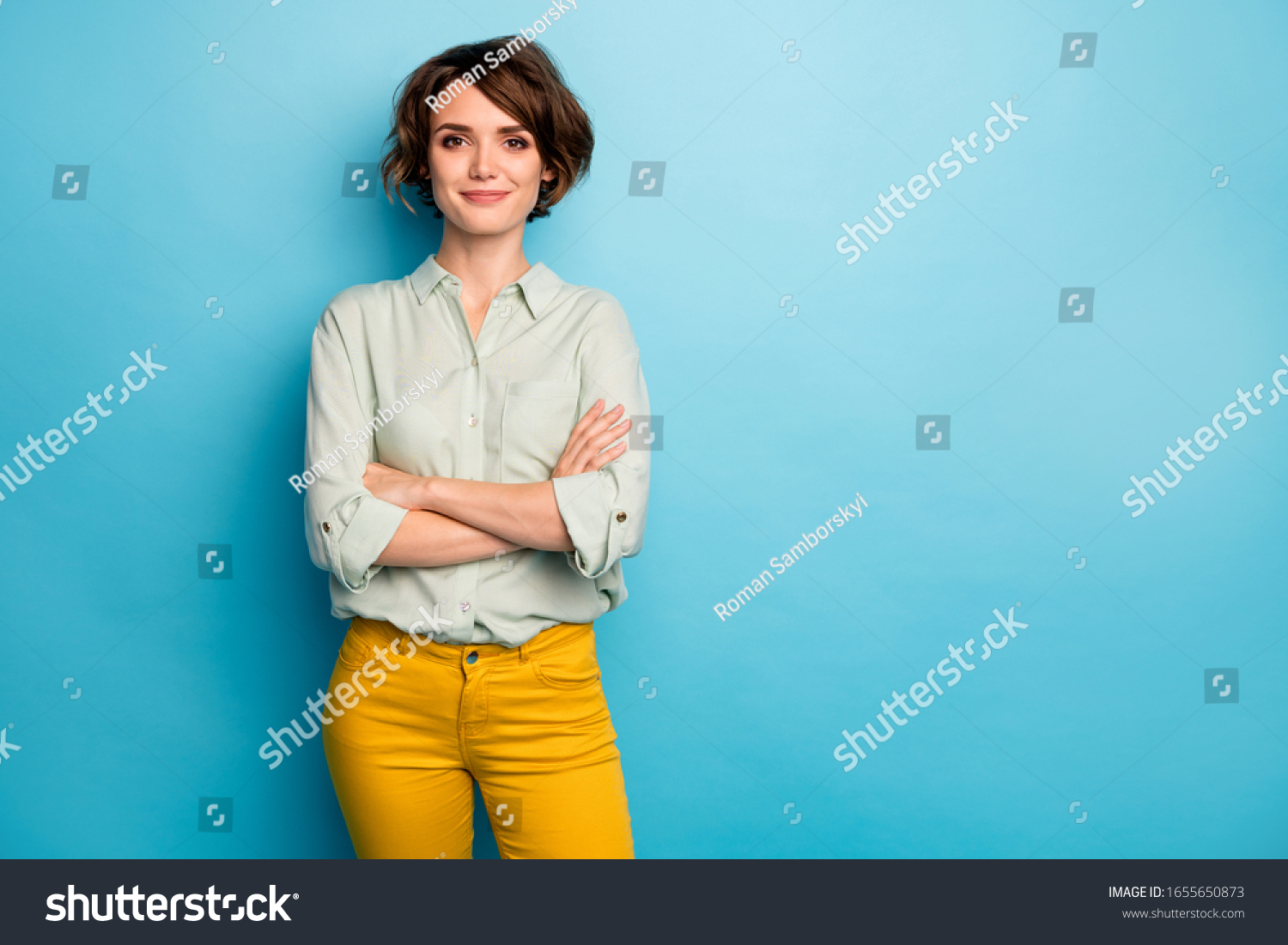 Photo of cool attractive business lady short hairstyle friendly smiling responsible person arms crossed wear casual green shirt yellow pants isolated blue color background #1655650873