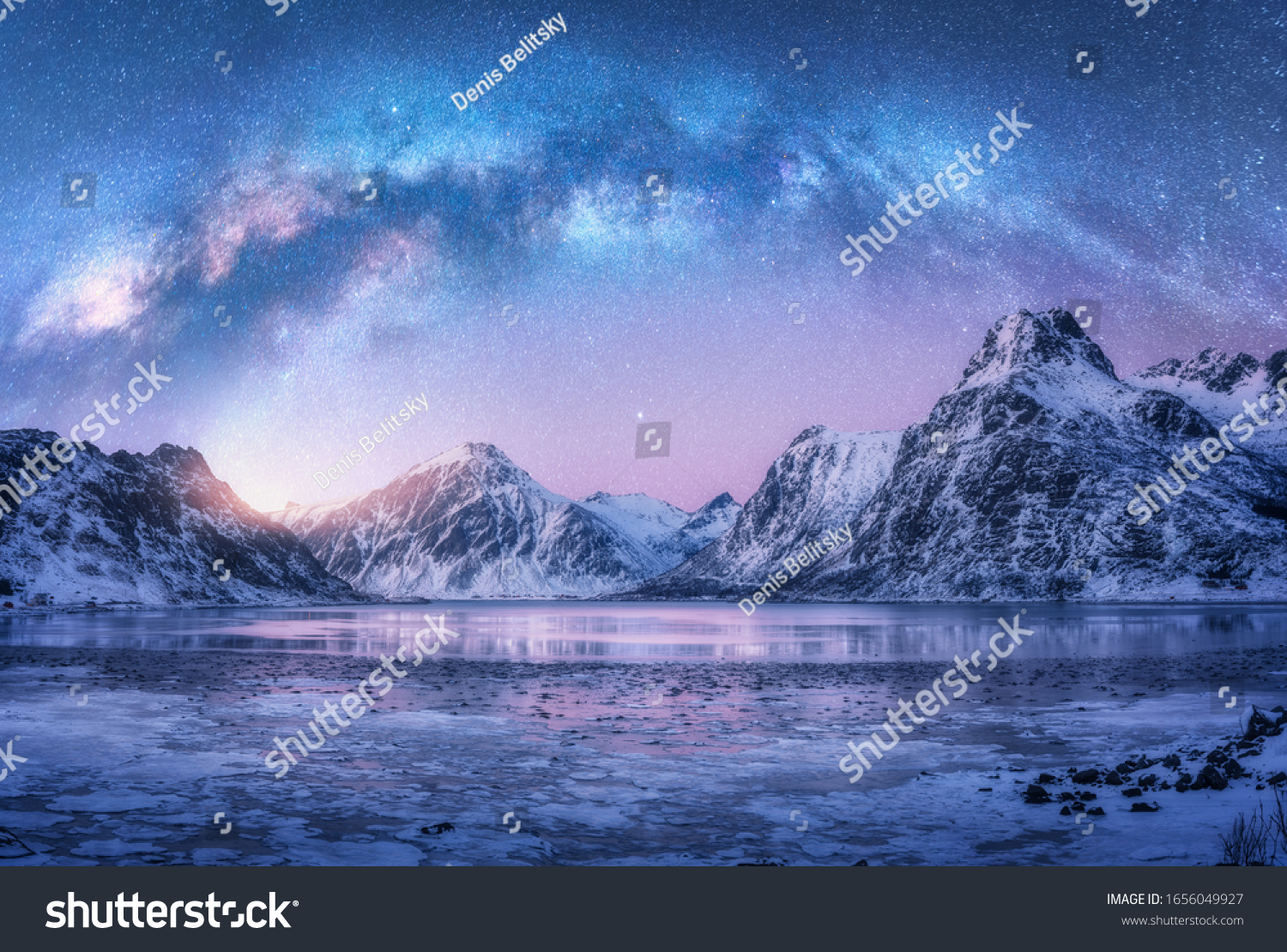 Milky Way above frozen sea coast and snow covered mountains in winter at night in Lofoten Islands, Norway. Arctic landscape with blue starry sky,  water, ice, snowy rocks, milky way. Space and galaxy #1656049927