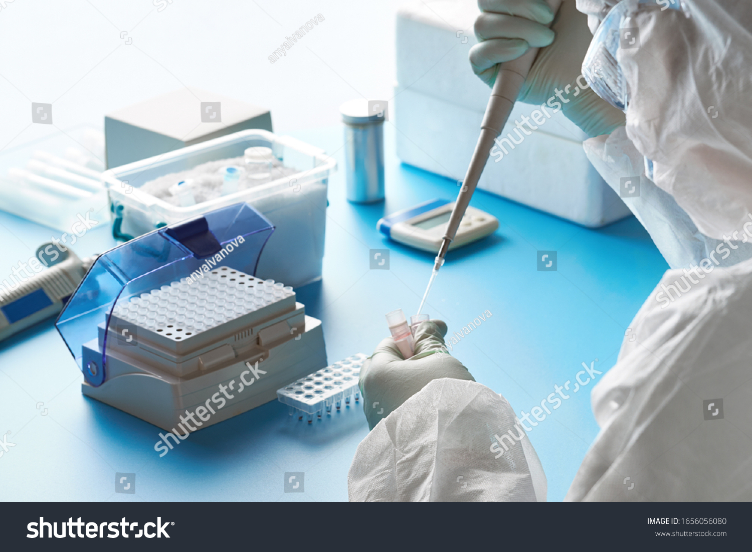 Epidemiologist in protective suit, mask and glasses works with patient swabs to detect specific region of 2019-nCoV virus causing Covid-19 viral pneumonia. SARS-COV-2 pcr diagnostics kit concept. #1656056080