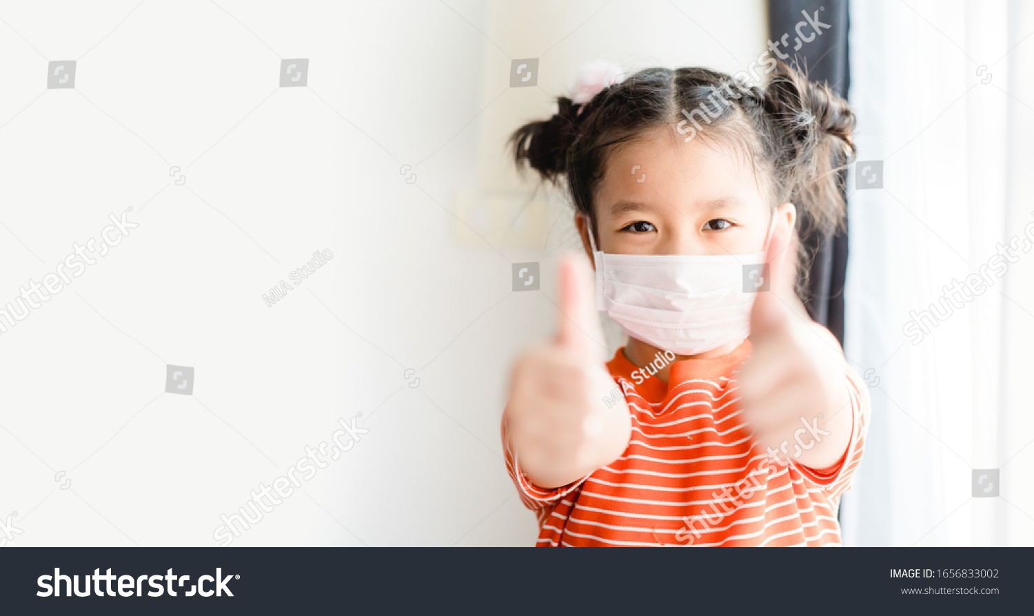 Coronavirus Covid-19 pm2.5.Online education.Little chinese girl wearing face mask show thumbs up for good and happy at home. Covid-19 coronavirus.Stay home.Social distancing.New normal behavior. #1656833002