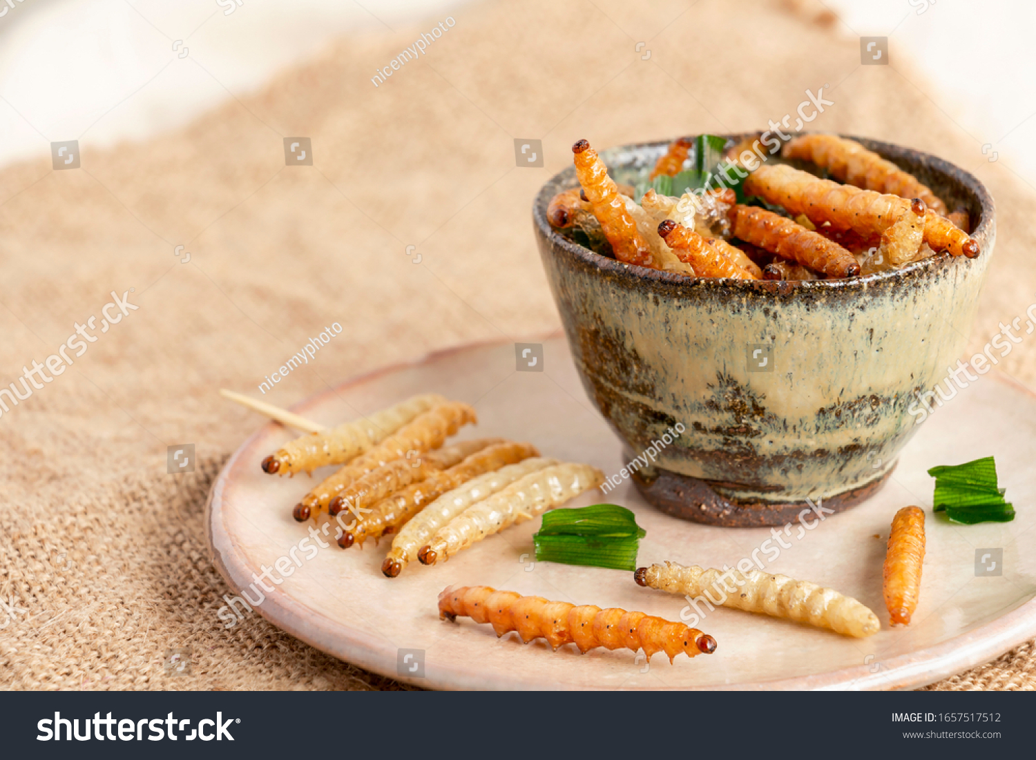 Food Insects: Bamboo worm or Bamboo Caterpillar insect fried crispy for eating as food items in bowl and plate ceramic on sackcloth, it is good source of protein edible for future food concept. #1657517512