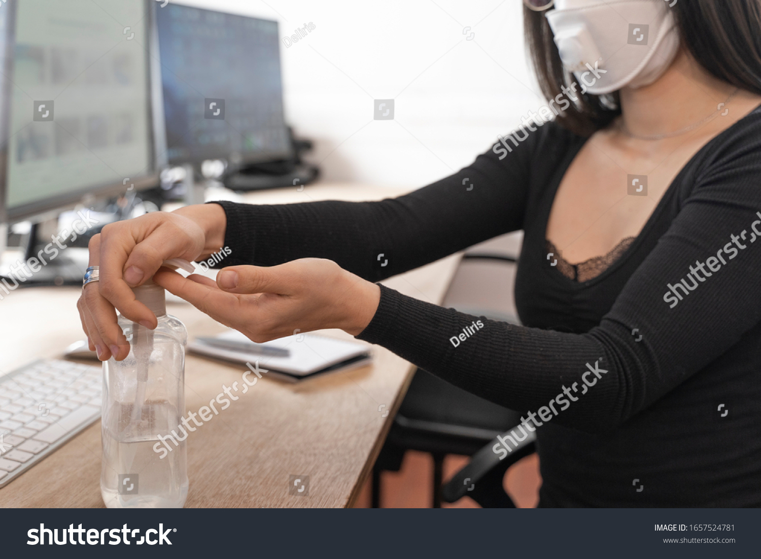Coronavirus. Woman cleaning her hands at the office. Sick with mask for corona virus. Workplace desk with computer. Woman spraying alcohol gel or antibacterial soap sanitizer. #1657524781
