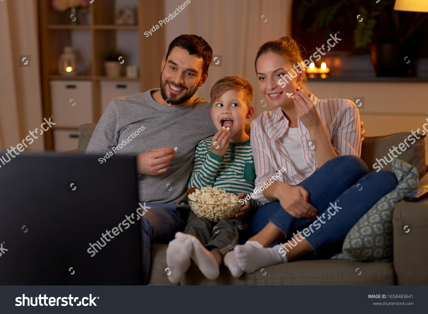 family, leisure and people concept - happy smiling father, mother and little son eating popcorn and watching tv at home in evening #1658483641